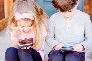 dwójka dzieci patrząca w smartfona